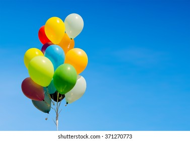 Colorful bunch of helium balloons isolated on background, with copy space
