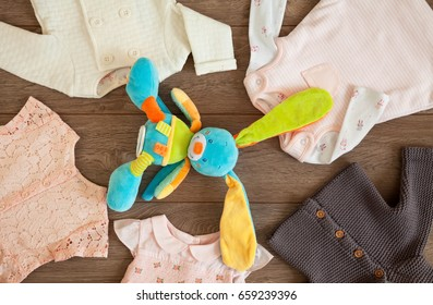 Colorful bunny toy and tiny baby girl clothes and jackets in a tabletop flat lay arrangement on brown wooden background.