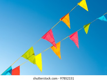 colorful bunting flags against a blue saturated sky