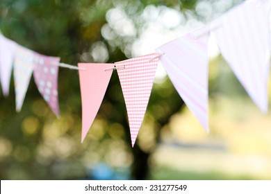 Colorful bunting flags against green trees