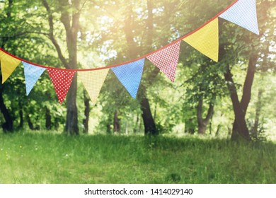 Colorful bunting flags hanging in park. Summer garden party. Outdoor birthday, wedding decoration. Midsummer, festa junina concept. Selective focus. Blurred grass and trees. Sunset haze.