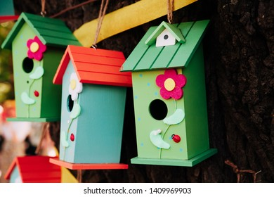 Colorful cages for birds. Wooden bird houses ornamented with flowers, placed on a tree.