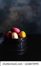 Colorful Cake macaron or macaroons on dark moody background. Macaron or Macaroon is sweet meringue-based confection.