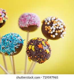 Colorful cake pops on a yellow background
