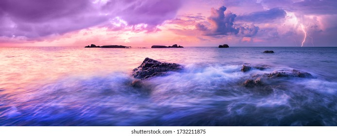 Colorful calm sea during sunset. A storm is approaching over the horizon. Colorful dark clouds in the air, electric discharges herald the coming storm.