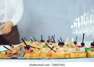 Colorful canape on skewers with vegetables and sausage on a slate plate. Tasty appetizer for a party or banquet. Selective focus