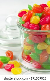 Colorful candied fruits in glass jar on white wooden background.