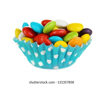 Colorful candies in cupcake case isolated on white