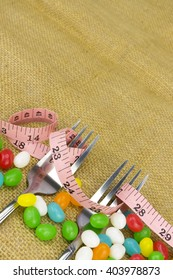 Colorful candies fork and tape measure with shallow depth of field (dof)-diet and healthy teeth concept
