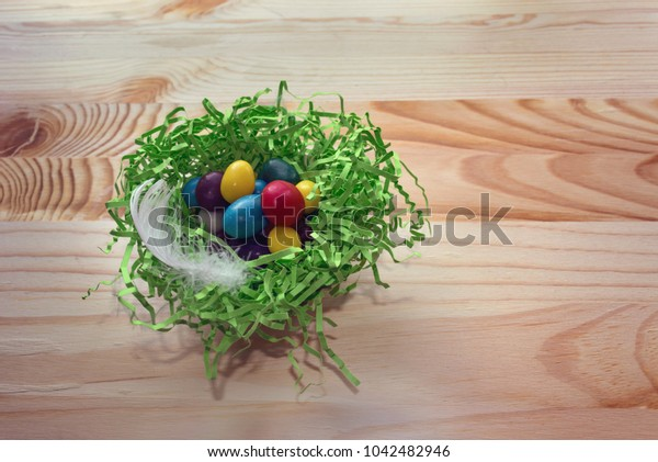 colorful candies in green nest with white feather on wooden background