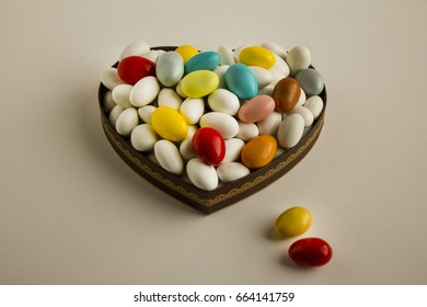 Colorful candies in heart shaped wooden plate