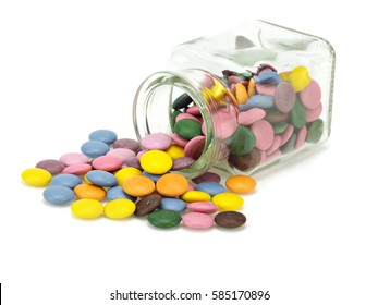 Colorful candies in jar on a white background