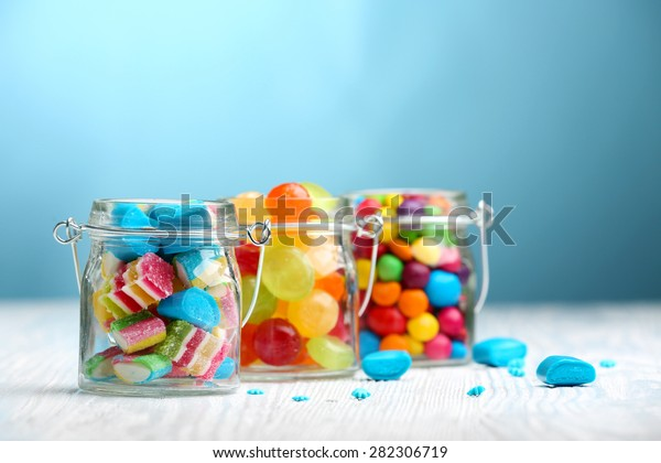 Colorful candies in jars on table on blue background background