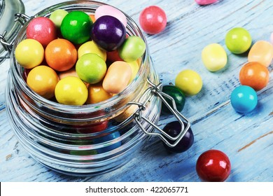 Colorful candies and lollipops in a jar on wooden background. focus on sweets and a glass jar