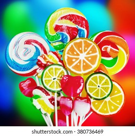 Colorful candies and lollipops on batskground balloons. focus on large lollipops