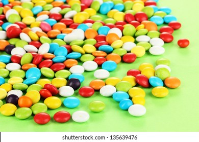 Colorful candies on green background