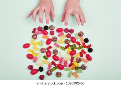 Colorful candies on pastel turquoise background. Kids hands are trying to get candies. Flat lay of sweets.