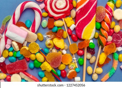 Colorful candies on table on blue background