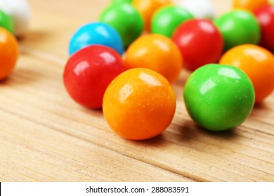 Colorful candies on wooden table, closeup