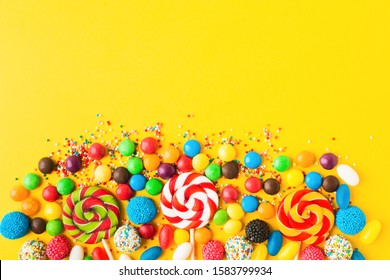 Colorful candies over yellow background. Top view. Flat lay. Copy space. Sweet mix for birthday or candy shop