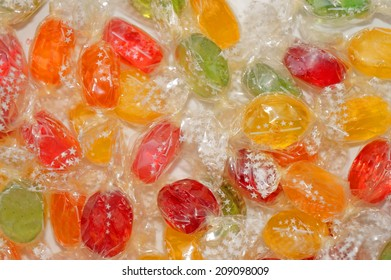 Colorful candies in transparent wrappers closeup