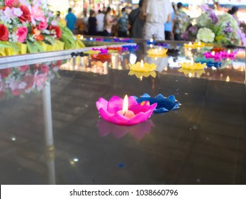 Colorful candles flame floating on the water. Funeral service concept. Selective focus and shallow depth of field.