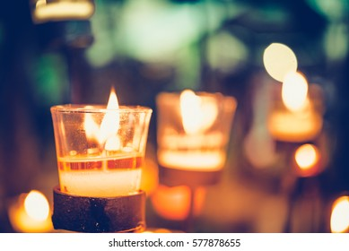 Colorful Candles light for Christmas candles burning at night. Abstract candles background. Golden light of candle flame with vintage retro tone.