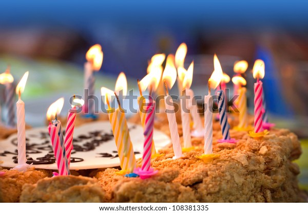 Colorful candles on  birthday cake above dark background