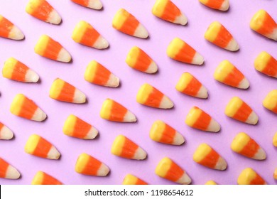 Colorful candy corns for Halloween party on color background, top view