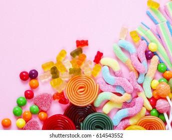 Colorful candy and fruit jelly sweets on a pink background