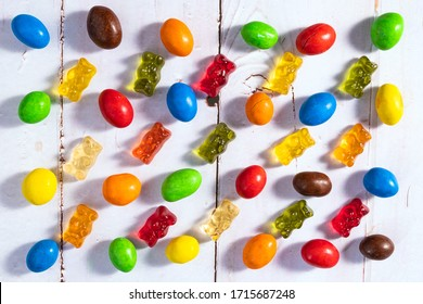 Colorful candy and gummi jelly on white wooden background