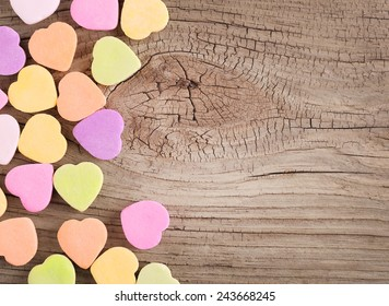 Colorful candy hearts on wooden background