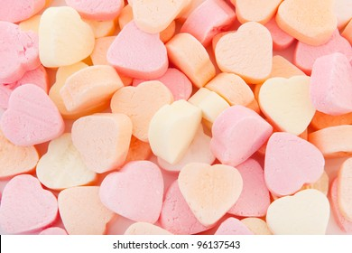 Colorful candy hearts in pink yellow and orange as background