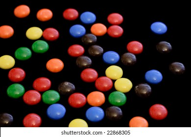 Colorful candy on black background - horizontal