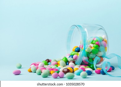Colorful candy are scattered on blue background. Gifts for Birthday or Happy Easter.