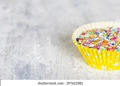 Colorful candy sprinkles in cupcake paper cases. For cake decorating. Selective focus