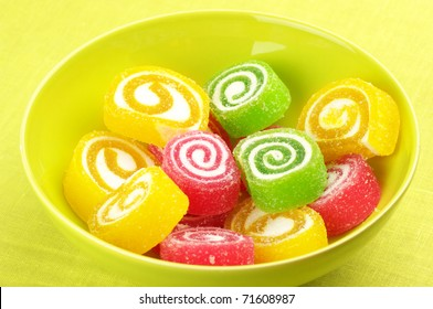Colorful candy in yellow bowl on yellow background.