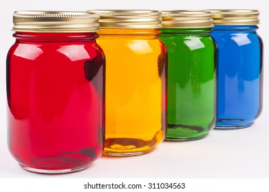 Colorful Canning Jars filled with brightly colored water - Red Yellow Green Blue
