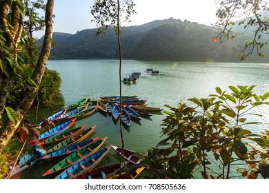 Colorful canoe boats at sunrise on Phewa Lake in Pokhara, Nepal.