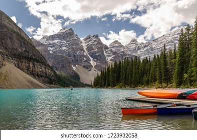 Colorful canoes on the lake in front of the mountains at Moraine Lake, Banff National Park