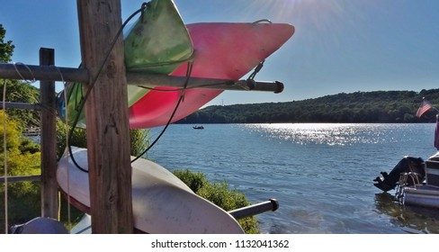 Colorful Canoes on Their Boat Racks Nearing Sunset with Deep Blue Water Views