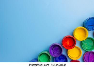 colorful cans with paint on blue background. copy space