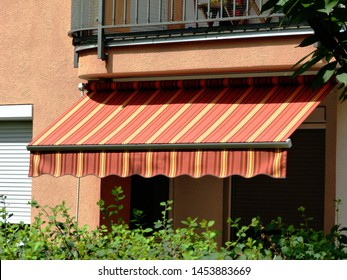 colorful canvas awning in yellow & orange over a residential balcony. sunny summer day. sun protection concept. UV exposure. warm color waterproof fabric material. green garden. selective focus.