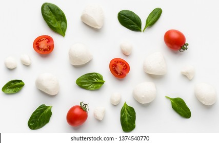 Colorful caprese ingredients pattern made of cherry tomatoes, basil and cheese on white background. Caprese salad recipe concept, top view