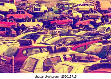 Colorful car wrecks top of each other in the scrap yard - Scrap
