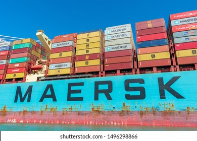 Colorful cargo shipping containers stacked aboard of container ship Maersk Line during cargo loading and unloading operation under blue sky - Oakland, California, USA - August 30, 2019