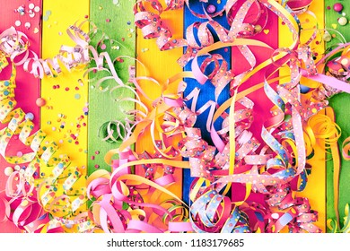Colorful carnival background with a tangle of pink streamers and ribbons on striped rainbow colored wood