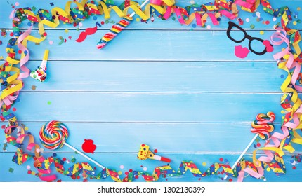 Colorful carnival or birthday background with streamers, confetti and other party accessoires on blue wooden planks