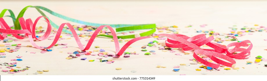 Colorful carnival confetti and serpentines on white wooden background, banner