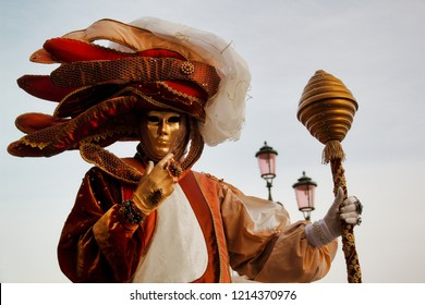 Colorful carnival gold-beige-brown mask and costume at the traditional festival in Venice, Italy